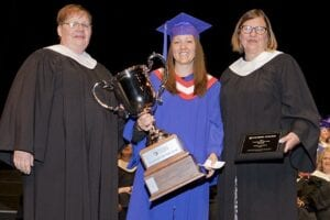 Debra Andrew holds her Student of the Year trophy, given by the hands of her Psych Nursing instructors.