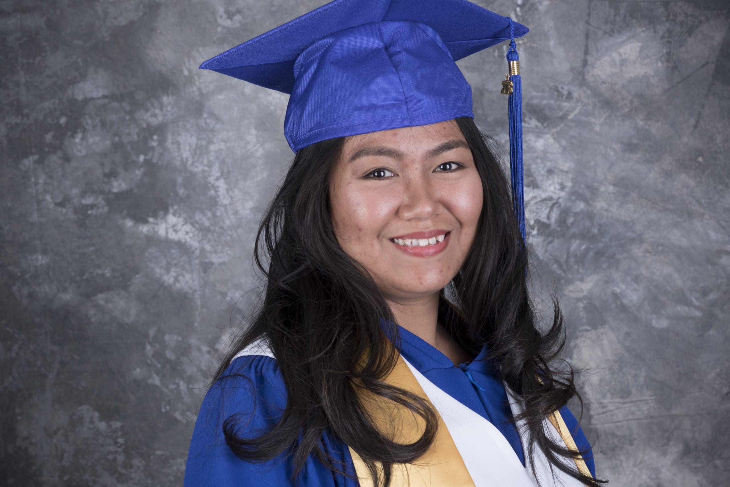 Faith Samson happy in a grad gown after completing her course as an Education Assistant.