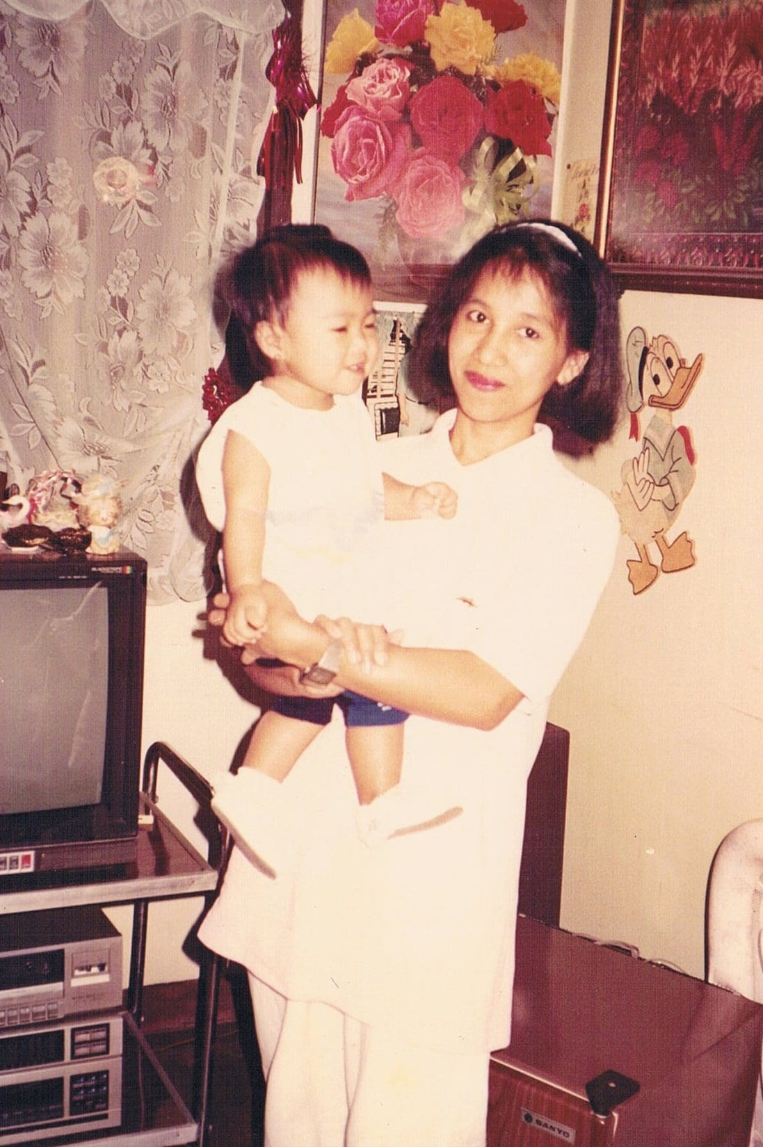 Faith's mother carrying her in her arms at their home country, the Philippines.